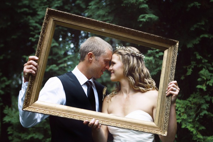 A bride and groom embrace in picture frame.